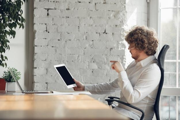 Пустой экран. кавказский молодой человек в деловой одежде, работающих в офисе. молодой предприниматель, менеджер, выполняющий задачи со смартфоном, ноутбуком, планшетом, проводит онлайн-конференцию. понятие о работе, образовании.