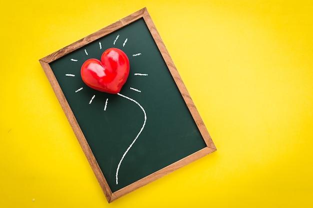 コルバックグラウンドで赤い心臓オブジェクトを持つ空白の画面の黒板
