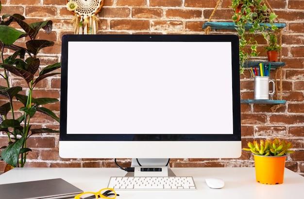 Компьютер пустой экран в офисной комнате с аксессуарами и копией пространства. кирпичная стена в фоновом режиме
