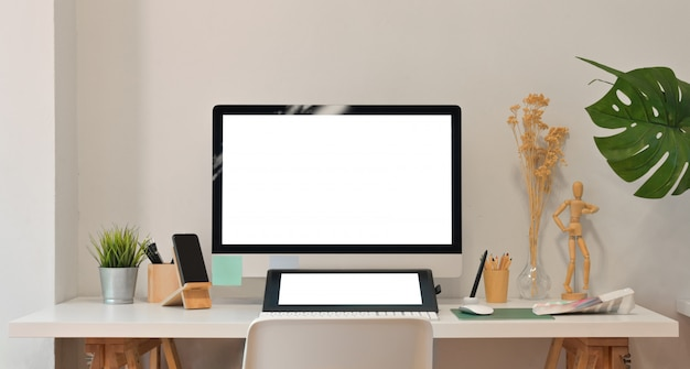 Blank screen computer and tablet in modern office room