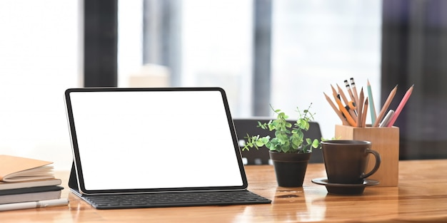 Blank screen computer tablet with keyboard case putting on wooden working desk with pencil holder, coffee cup, potted plant, stack of books and pen over neat living room.