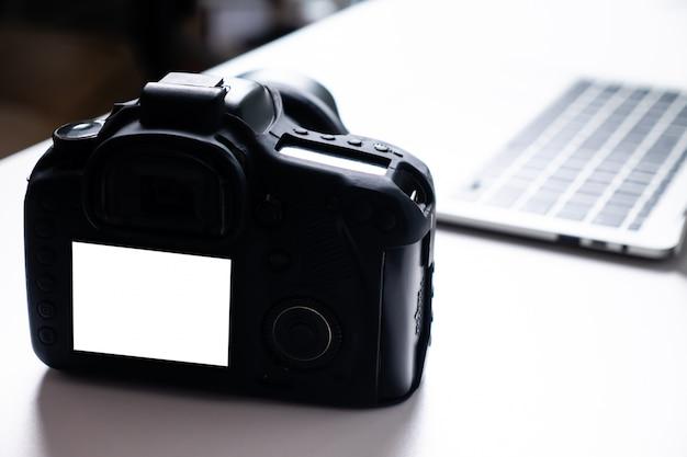 空白の画面のデジタルカメラとテーブルの上のコンピューターのラップトップ。