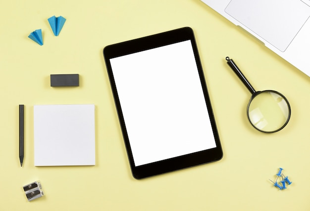 Blank screen digital tablet with office supplies on yellow backdrop