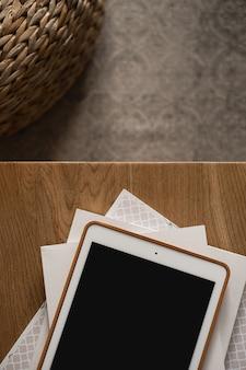 木製のテーブルに空白の画面が表示されます。フラットレイ、トップビューミニマリストブログ、ウェブサイト、アプリテンプレート
