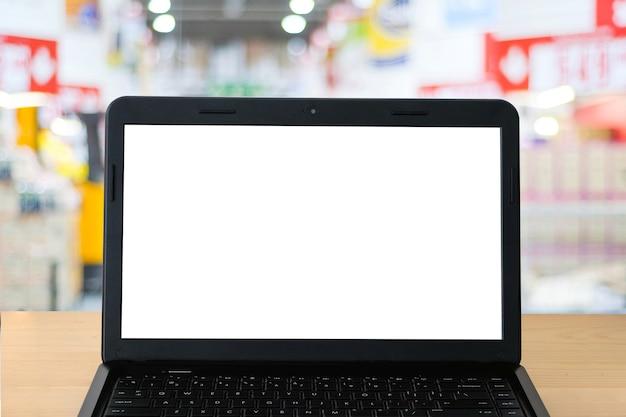 Пустой экран labtop и размытие фона супермаркета