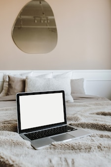 Blank screen laptop on bed with pillows in front of beige wall