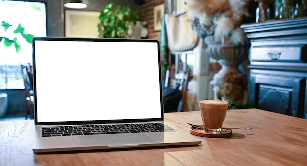 Blank screen laptop and coffee cup putting together on the wooden table with the beautiful classic decorate room