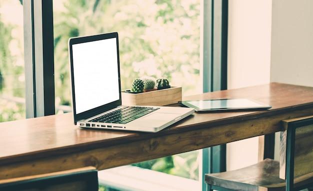 카페 레스토랑에서 창 근처 나무 의자 테이블에 빈 화면 노트북 컴퓨터와 태블릿