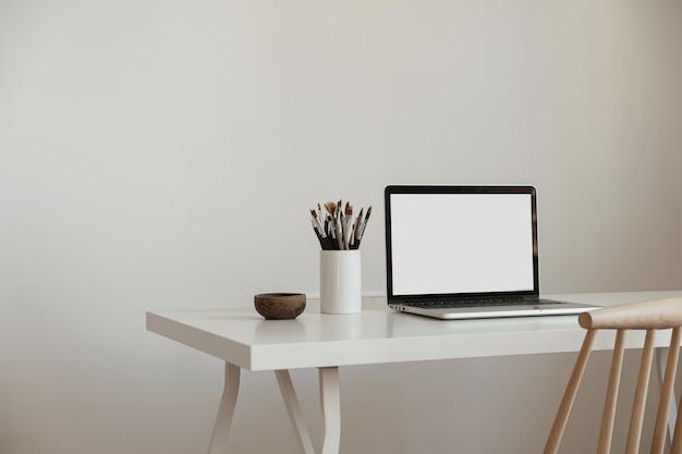 空白の画面のラップトップコンピューター。ホームオフィスデスクテーブルワークスペース。スカンジナビアのインテリアデザイン。