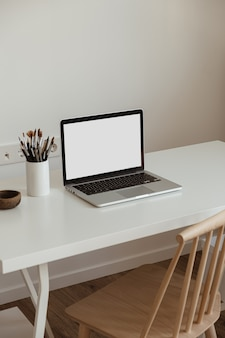 空白の画面のラップトップコンピューター。ホームオフィスデスクテーブルワークスペース