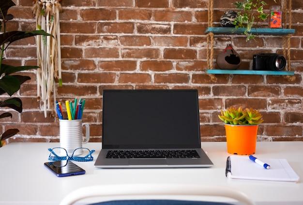 Пустой экран портативного компьютера в офисной комнате с аксессуарами и копией пространства кирпичная стена i