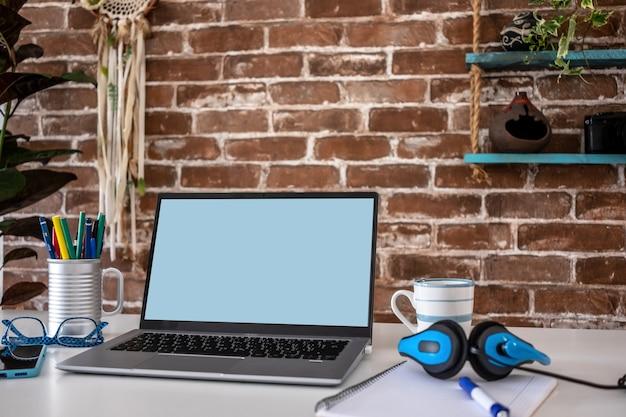 Пустой экран портативного компьютера в офисной комнате с аксессуарами