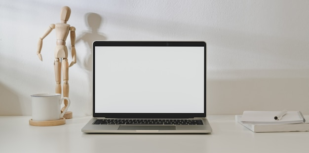 Blank screen laptop computer in minimal workplace with  office supplies and decorations