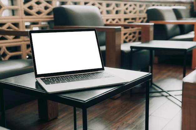 テーブルの上の空白の画面のラップトップコンピューター
