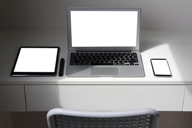Blank screen laptop computer and smart phone and digital tablet and stylus pen is on wooden desk.
