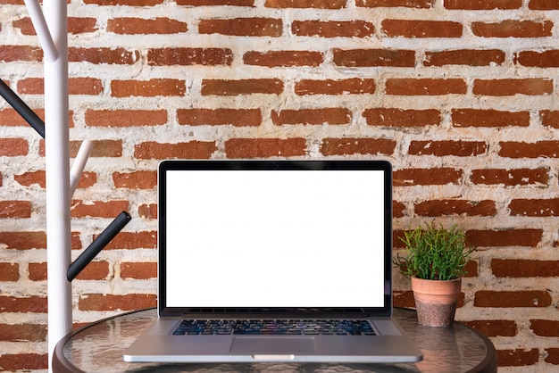 Blank screen of laptop computer on table with red brick wall