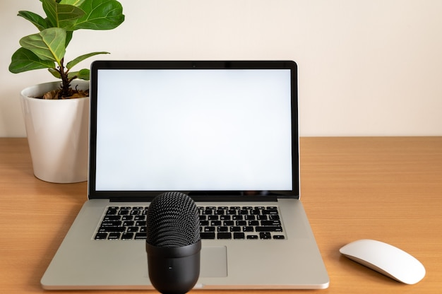 Blank screen of laptop computer with microphone and fiddle fig tree pot on wooden table