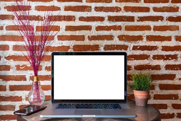 Blank screen of laptop computer with smart phone on table with red brick wall