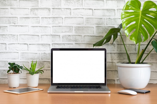 Blank screen of laptop computer with tablet, mobile phone, mouse and monstera plant pots on wooden table