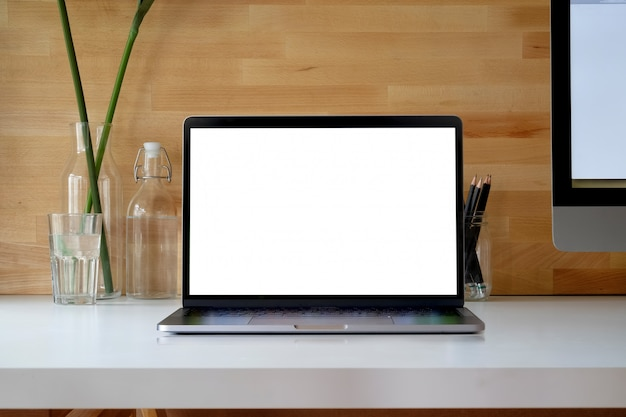 Blank screen laptop and desktop computer on white wood.