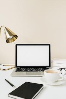 空白の画面のラップトップ。ベージュの背景にコーヒー、ランプ、メガネ、ノートブックとホームオフィスデスクテーブルワークスペース。