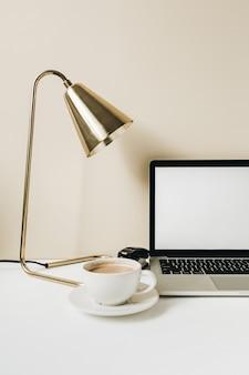 空白の画面のラップトップ。コーヒー、ベージュのランプとホームオフィスデスクテーブルワークスペース
