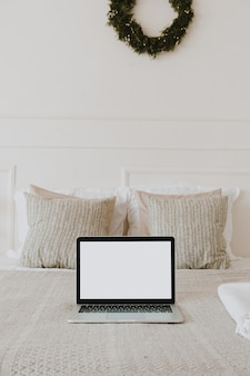 枕とリネンとベッドの上の空白の画面のラップトップ