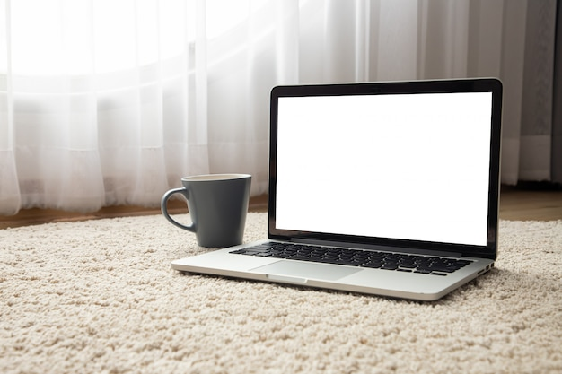 Blank screen laptop, notebook and morning coffee cup on doormat floor texture background.
