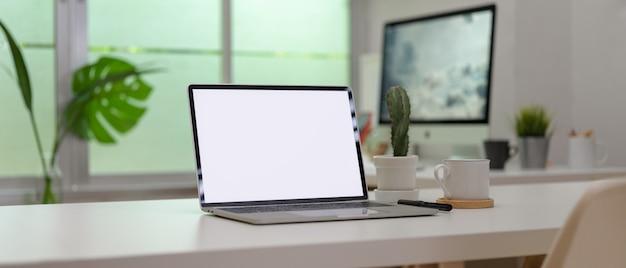近代的な事務室の事務用品と白い机の上の空白の画面ノートパソコン
