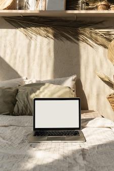 空白の画面のラップトップ。壁に暖かい日光の影