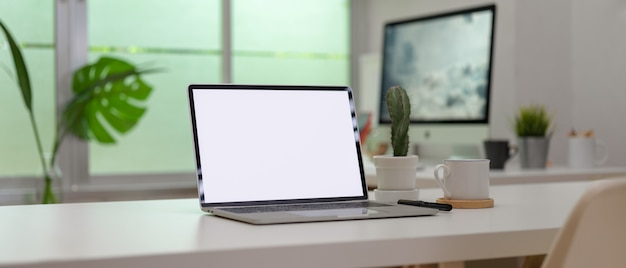 Blank screen laptop on white desk with office supplies in modern office room