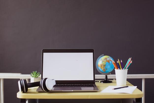 アクセサリーと木製の机の上に静止した空白の画面のラップトップ