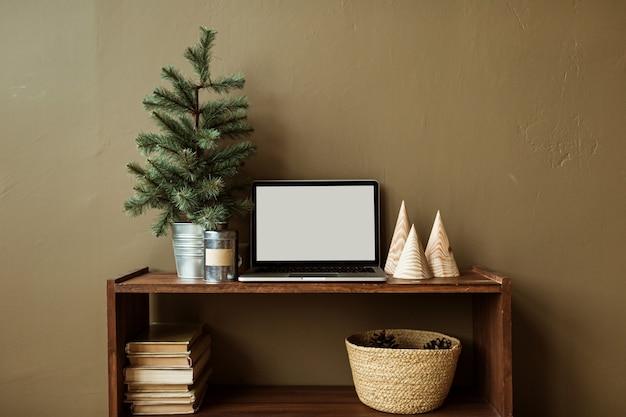 전나무 나무, 책, 짚 바구니 장식 나무 스탠드에 복사 공간이있는 빈 화면 노트북