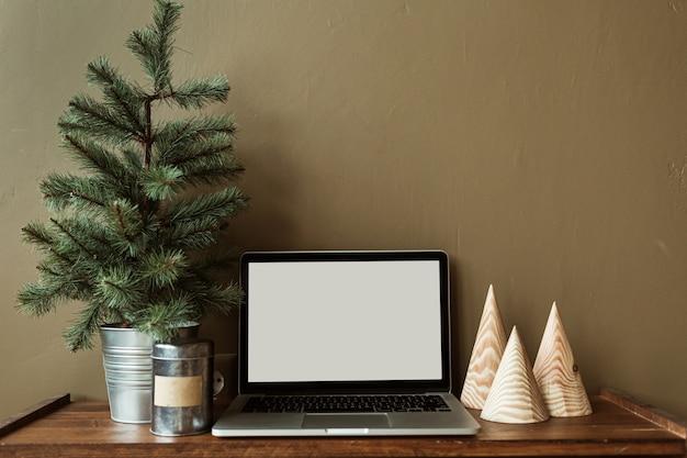전나무 나무로 장식 된 나무 스탠드에 복사 공간을 가진 빈 화면 노트북.