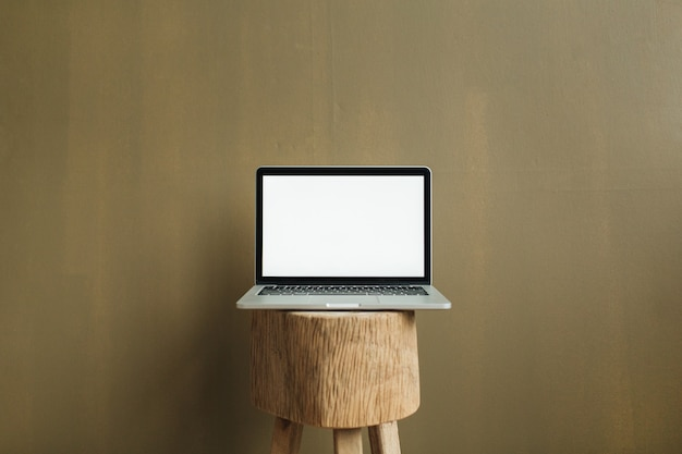 Blank screen laptop on wooden stool at tan olive