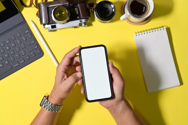Blank screen mobile phone in man hands on workspace