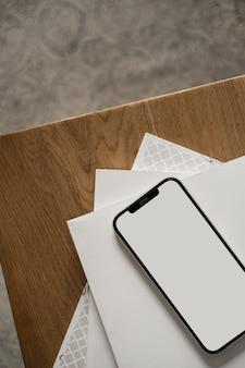 木製のテーブルの上の空白の画面の携帯電話