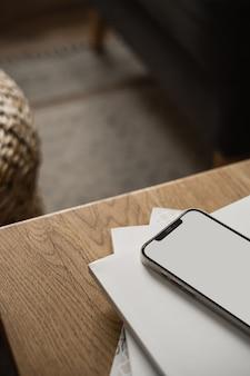 空白の画面の携帯電話、木製のテーブルとカーペットの上の紙のシーツ