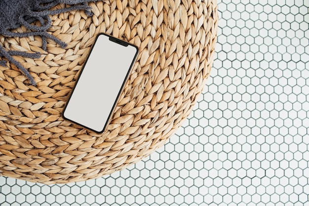 Blank screen mobile phone with empty copy space mockup on rattan puff and mosaic tile