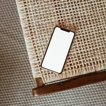등나무 의자에 빈 화면 스마트 폰