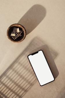 空白の画面のスマートフォン。スタイル付きのホームオフィスデスクワークスペース。