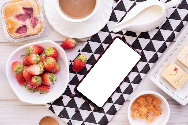 Blank screen on smartphone, cellphone, tablet with sweet dessert and strawberries