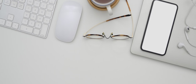 Blank screen smartphone above schedule book on white office desk with computer devices, glasses, cup and copy space