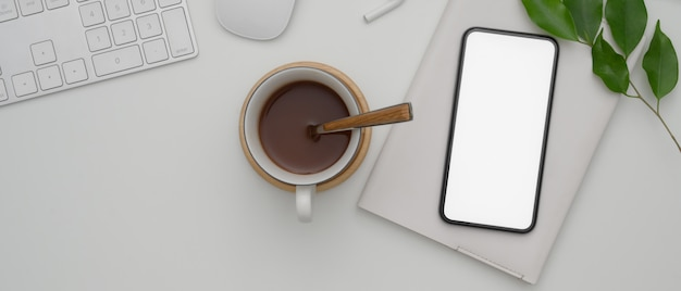 Blank screen smartphone above schedule book on white office desk with computer devices and hot cocoa cup
