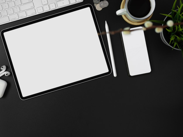Blank screen smartphone, tablet, other supplies, decorations and copy space on dark modern worktable