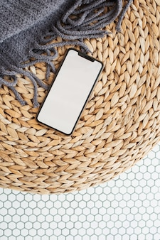 籐のパフ、格子縞、モザイクタイルに空のコピースペースのモックアップを備えた空白の画面のスマートフォン