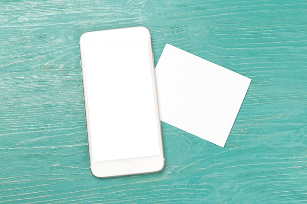 Blank screen smartphone on wooden table.