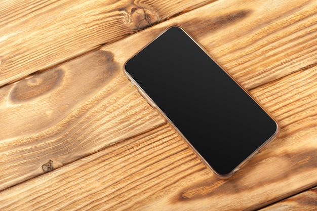 Blank screen smartphone on wooden