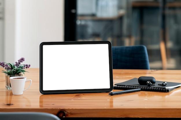 空白の画面のタブレットと、オフィス ルームのコピー スペースで木製のテーブル上のガジェット