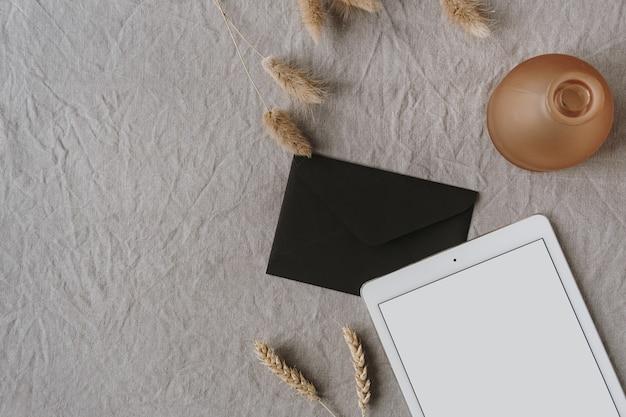 空白の画面のタブレット、封筒、装飾、灰色の洗浄されたリネン布の耳小麦の耳の茎。フラットレイ、上面図